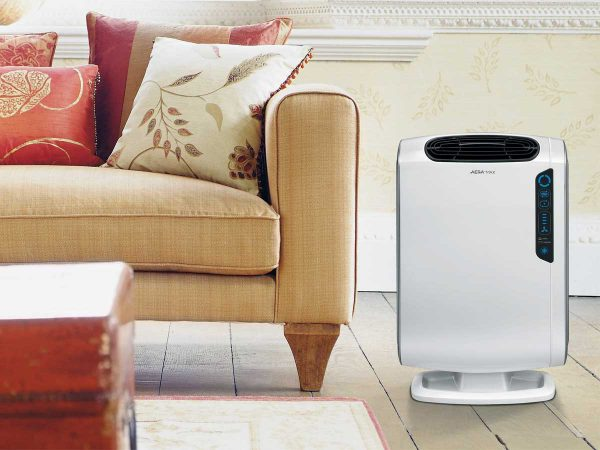 Fellowes® AeraMax DX55 Air Purifier next to sofa